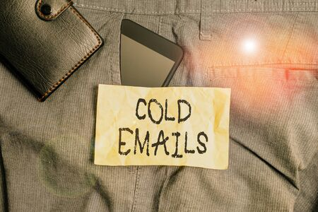Writing note showing Cold Emails. Business concept for unsolicited email sent to a receiver without prior contact Smartphone device inside trousers front pocket with wallet