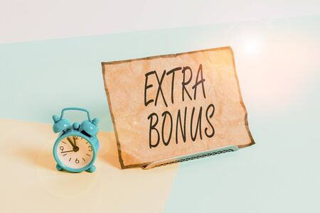 Conceptual hand writing showing Extra Bonus. Concept meaning an extra amount of money that is added to someone s is pay Alarm clock beside a Paper sheet placed on pastel backdrop