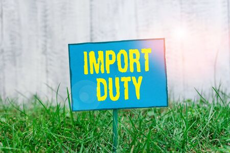 Conceptual hand writing showing Import Duty. Concept meaning tax imposed by a government on goods from other countries Plain paper attached to stick and placed in the grassy land Archivio Fotografico