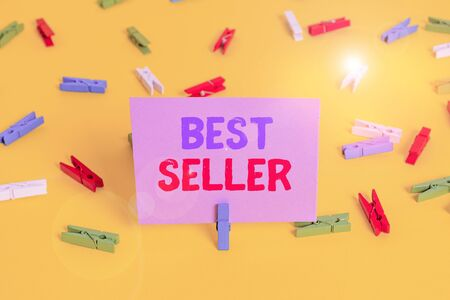 Handwriting text writing Best Seller. Conceptual photo new book or other product that has sold a great number of copies Colored clothespin papers empty reminder yellow floor background office