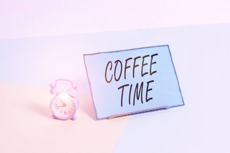 Conceptual hand writing showing Coffee Time. Concept meaning a short period of time in which you stop working to rest Alarm clock beside a Paper sheet placed on pastel backdrop Archivio Fotografico