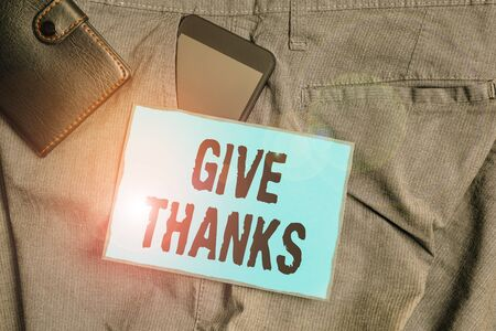 Handwriting text writing Give Thanks. Conceptual photo express gratitude or show appreciation Acknowledge the kindness Smartphone device inside trousers front pocket with wallet and note paper
