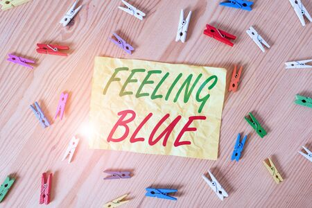 Writing note showing Feeling Blue. Business concept for Feeling of desperation because of sadness or missing someone Colored clothespin papers empty reminder wooden floor background office