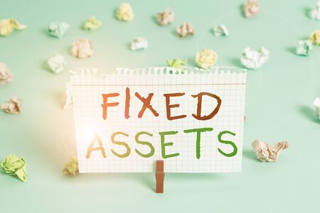 Word writing text Fixed Assets. Business photo showcasing longterm tangible piece of property or equipment a firm owns Colored crumpled rectangle shaped reminder paper light blue background