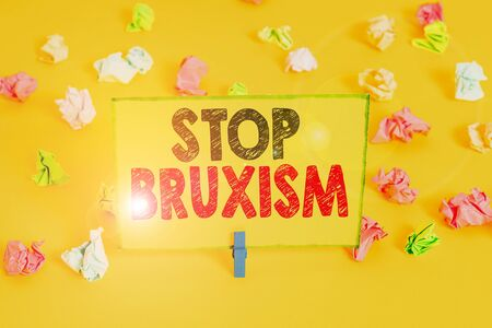 Word writing text Stop Bruxism. Business photo showcasing put an end to a condition which you grind or clench the teeth Colored crumpled papers empty reminder white floor background clothespin