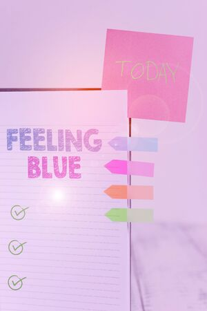 Writing note showing Feeling Blue. Business concept for Feeling of desperation because of sadness or missing someone Hard cover note book sticky note arrow banner inserted clear background