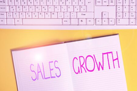 Conceptual hand writing showing Sales Growth. Concept meaning ability to increase revenue over a fixed period of time Copy space on notebook on yellow background with keyboard on table