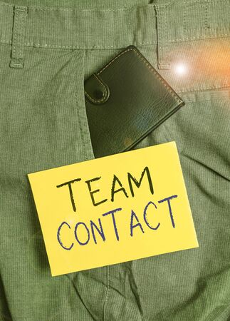 Writing note showing Team Contact. Business concept for The interaction of the individuals on a team or group Small wallet inside trouser front pocket near notation paper
