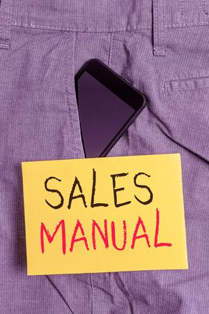 Word writing text Sales Manual. Business photo showcasing set of printed materials containing product descriptions Smartphone device inside formal work trousers front pocket near note paper 免版税图像