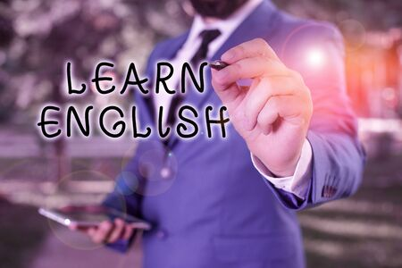 Text sign showing Learn English. Business photo text gain acquire knowledge in new language by study Businessman holds laptop and pen pointing into the copy space