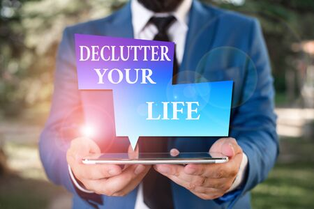 Word writing text Declutter Your Life. Business photo showcasing To eliminate extraneous things or information in life Businessman in blue suite with a tie holds lap top in hands