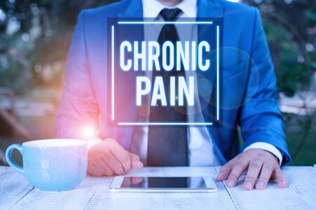 Writing note showing Chronic Pain. Business concept for pain that is ongoing and usually lasts longer than six months Businessman with pointing finger in front of him
