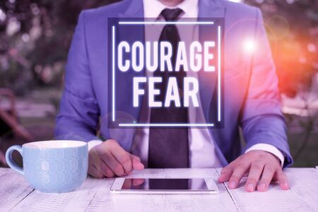 Writing note showing Courage Fear. Business concept for quality of mind that enables a demonstrating to face difficulty Businessman with pointing finger in front of him
