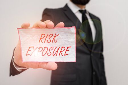 Writing note showing Risk Exposure. Business concept for the quantified potential loss that might occur in a business Male human wear formal work suit with office look hold book