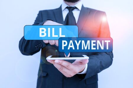 Conceptual hand writing showing Bill Payment. Concept meaning To give money to in return for goods or services rendered Male human wear formal work suit hold smartphone using hand