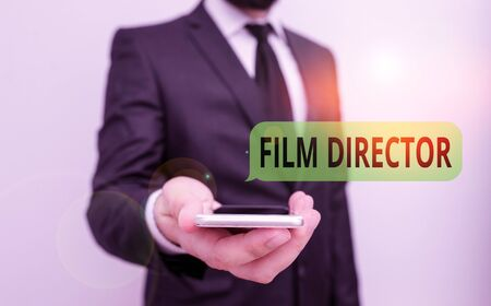 Word writing text Film Director. Business photo showcasing a demonstrating who is in charge of making and directing a film Male human wear formal work suit hold smart hi tech smartphone use one hand