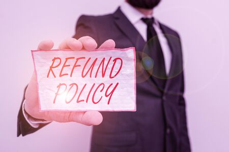 Writing note showing Refund Policy. Business concept for refund or exchange defective merchandise previously buy Male human wear formal work suit with office look hold book