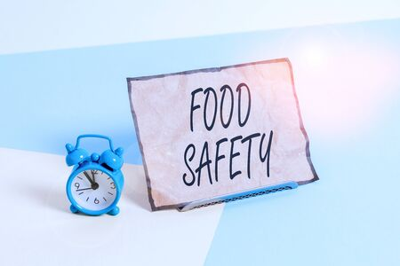 Conceptual hand writing showing Food Safety. Concept meaning conditions and practices that preserve the quality of food Alarm clock beside a Paper sheet placed on pastel backdrop