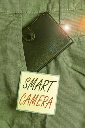 Text sign showing Smart Camera. Business photo showcasing individual image processing systems designed to automate Small little wallet inside man trousers front pocket near notation paper