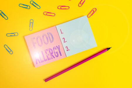 Word writing text Food Allergy. Business photo showcasing an abnormal immune response after eating a certain food Colored square blank sticky notepads pencil clips plain color background