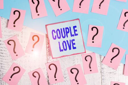 Conceptual hand writing showing Couple Love. Concept meaning two showing who love each other very much Feeling pleasure Crumbling papers with thick cardboard on the wooden table