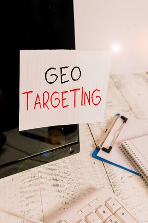 Writing note showing Geo Targeting. Business concept for method of determining the geolocation of a website visitor Note paper taped to black computer screen near keyboard and stationary