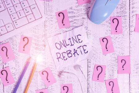 Text sign showing Online Rebate. Business photo text Return of a portion of a purchase price by a seller to a buyer Writing tools, computer stuff and scribbled paper on top of wooden table
