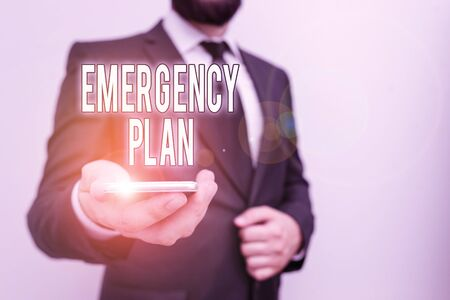 Handwriting text Emergency Plan. Conceptual photo course of action to mitigate the damage of potential events Male human wear formal work suit hold smart hi tech smartphone use one hand