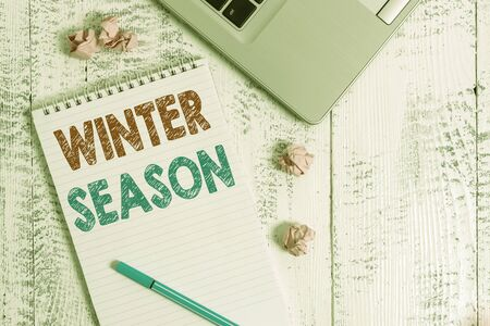 Conceptual hand writing showing Winter Season. Concept meaning the coldest season of the year in polar and temperate zones Laptop ruled spiral notepad crushed paper balls wooden table Stockfoto