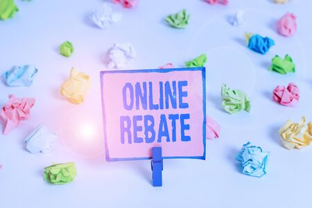 Text sign showing Online Rebate. Business photo text Return of a portion of a purchase price by a seller to a buyer Colored crumpled papers empty reminder white floor background clothespin