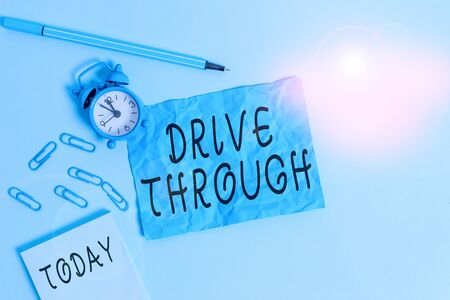 Handwriting text writing Drive Through. Conceptual photo place where you can get type of service by driving through it Alarm clock clips notepad blank crushed sheet marker sky colored background