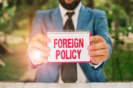 Handwriting text Foreign Policy. Conceptual photo a government strategy in dealing with other nations Man holds empty paper with copy space in front of him