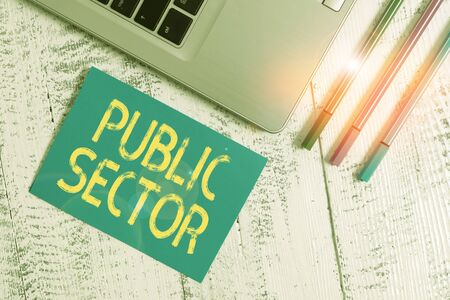 Text sign showing Public Sector. Business photo text the part of an economy that is controlled by the state Trendy metallic laptop blank sticky pad three pens lying vintage table Banque d'images