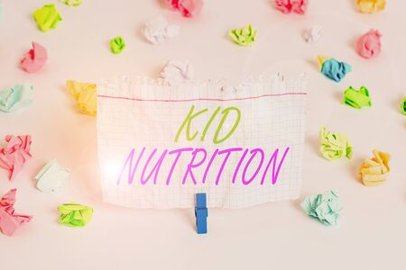 Handwriting text writing Kid Nutrition. Conceptual photo A healthy diet for children to help them grow and learn Colored crumpled papers empty reminder white floor background clothespin