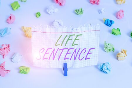 Handwriting text writing Life Sentence. Conceptual photo the punishment of being put in prison for a very long time Colored crumpled papers empty reminder white floor background clothespin
