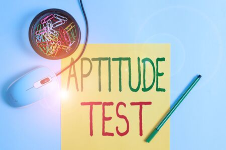 Writing note showing Aptitude Test. Business concept for designed to determine a demonstrating ability in a particular skill Notebook and stationary with gadgets above pastel backdrop Фото со стока