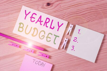 Writing note showing Yearly Budget. Business concept for A plan for a company expenditures for a fiscal year Colored clothespin papers empty reminder wooden floor background office