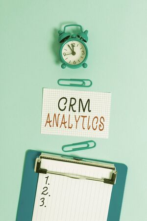 Word writing text Crm Analytics. Business photo showcasing applications used to evaluate an organization customer data Alarm clock clipboard squared blank paper sheet clips colored background
