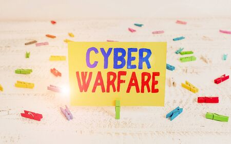 Conceptual hand writing showing Cyber Warfare. Concept meaning activity of using the internet to attack a country computers Green clothepin white wood background reminder office supply
