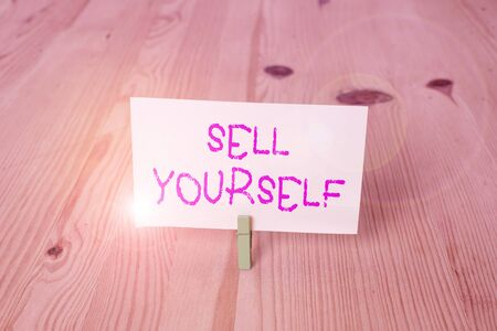 Conceptual hand writing showing Sell Yourself. Concept meaning to make yourself seem impressive or notable to other showing Wooden floor background green clothespin groove slot office