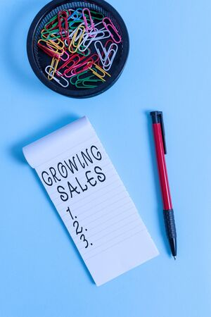 Conceptual hand writing showing Growing Sales. Concept meaning Average sales volume of a company products has grown Notebook and stationary with mouse above pastel backdrop Archivio Fotografico