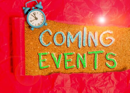Text sign showing Coming Events. Business photo showcasing happening or appearing soon Upcoming Forthcoming event Alarm clock and torn cardboard placed above a wooden classic table backdrop