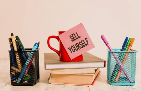 Word writing text Sell Yourself. Business photo showcasing to make yourself seem impressive or notable to other showing Coffee cup blank sticky note stacked books pen metal holders wooden table