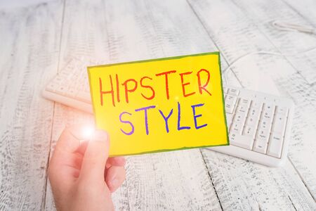 Handwriting text Hipster Style. Conceptual photo Fashion choices and music interests fall outside the majority man holding colorful reminder square shaped paper white keyboard wood floor Stock Photo