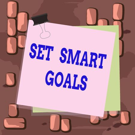 Word writing text Set Smart Goals. Business photo showcasing list to clarify your ideas focus efforts use time wisely Paper stuck binder clip colorful background reminder memo office supply