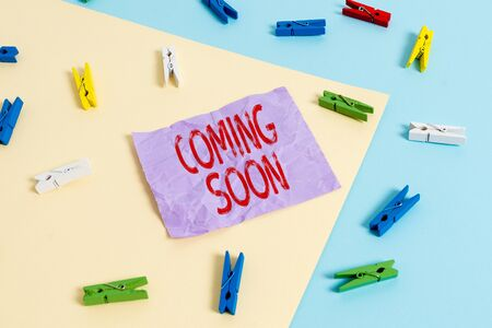 Text sign showing Coming Soon. Business photo showcasing event or action that will happen after really short time Colored clothespin paper empty reminder yellow blue floor background office