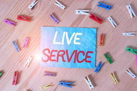 Text sign showing Live Service. Business photo text Extending or providing help to others in verbal or action way Colored clothespin papers empty reminder wooden floor background office
