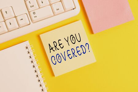 Writing note showing Are You Covered Question. Business concept for asking showing if they had insurance in work or life Empty papers with copy space on yellow background table