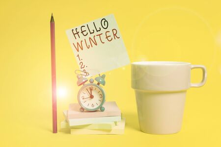 Word writing text Hello Winter. Business photo showcasing coldest season of the year in polar and temperate zones Alarm clock coffee cup note stacked notepads pencil colored background Stock Photo