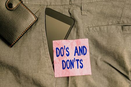 Text sign showing Dos And Don tS. Business photo showcasing Rules or customs concerning some activity or actions Smartphone device inside trousers front pocket with wallet and note paper